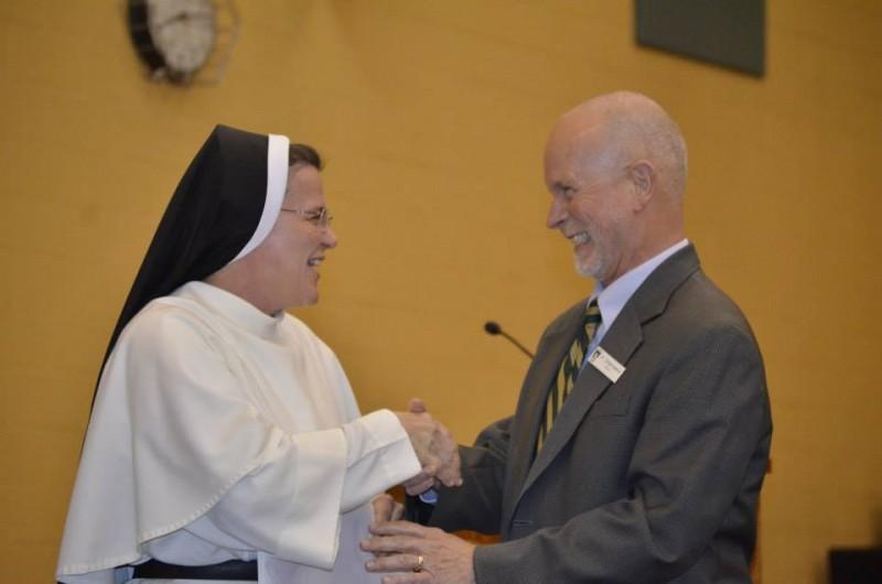 Pricipal Sr. Mary Jordan gives Rick the first-ever, Christ the Teacher award.