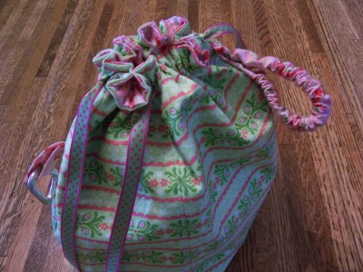 Wrist band loop for walking and knitting, ribbon drawstring, and pretty fabric on the outside.